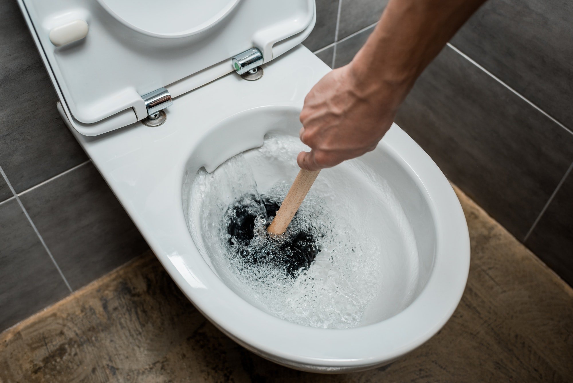 cropped view of plumber using plunger in toilet bowl during flushing in modern restroom with grey
