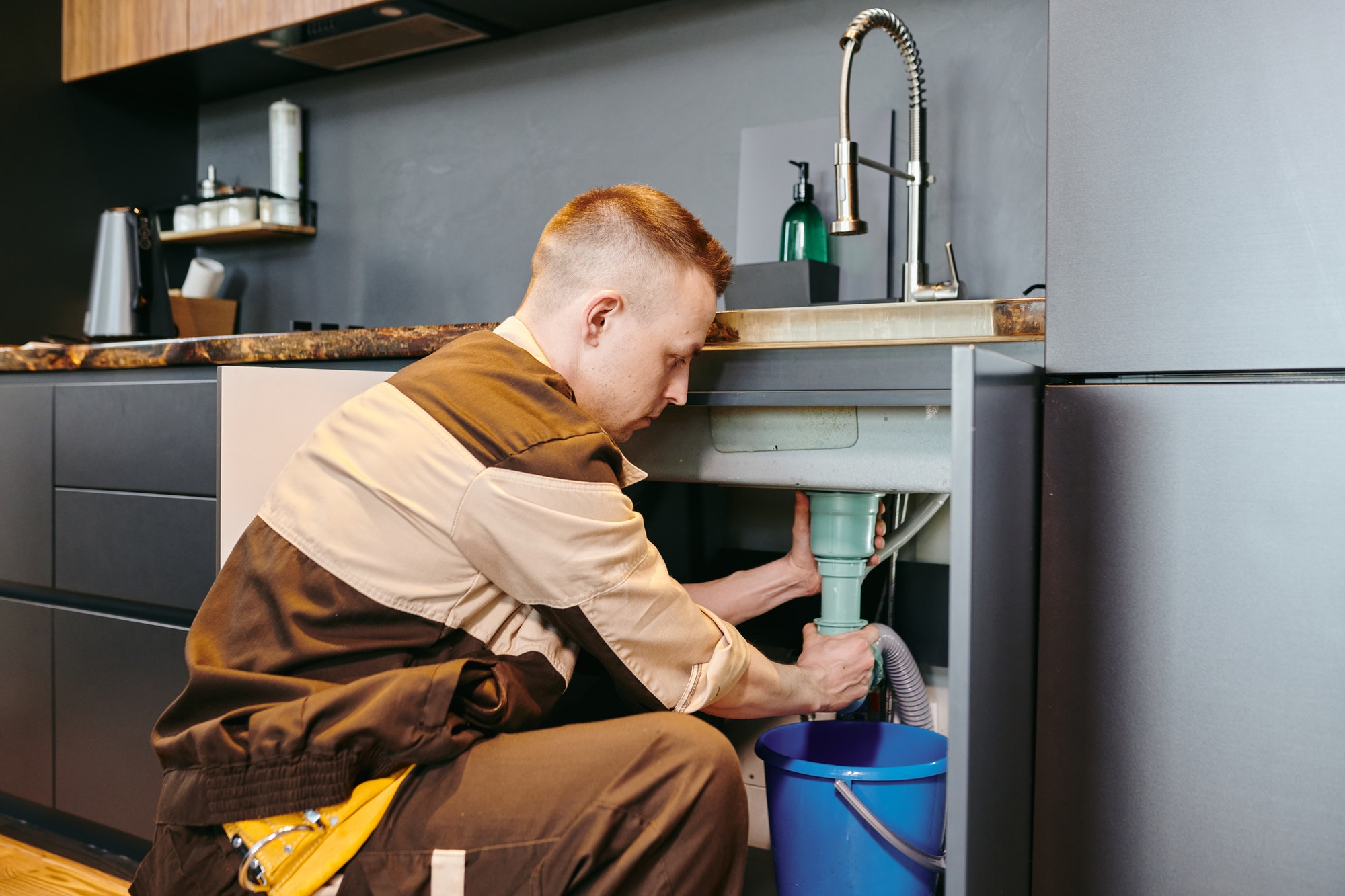 A man in uniform checking plumbing equipment after repairing in the kitchen