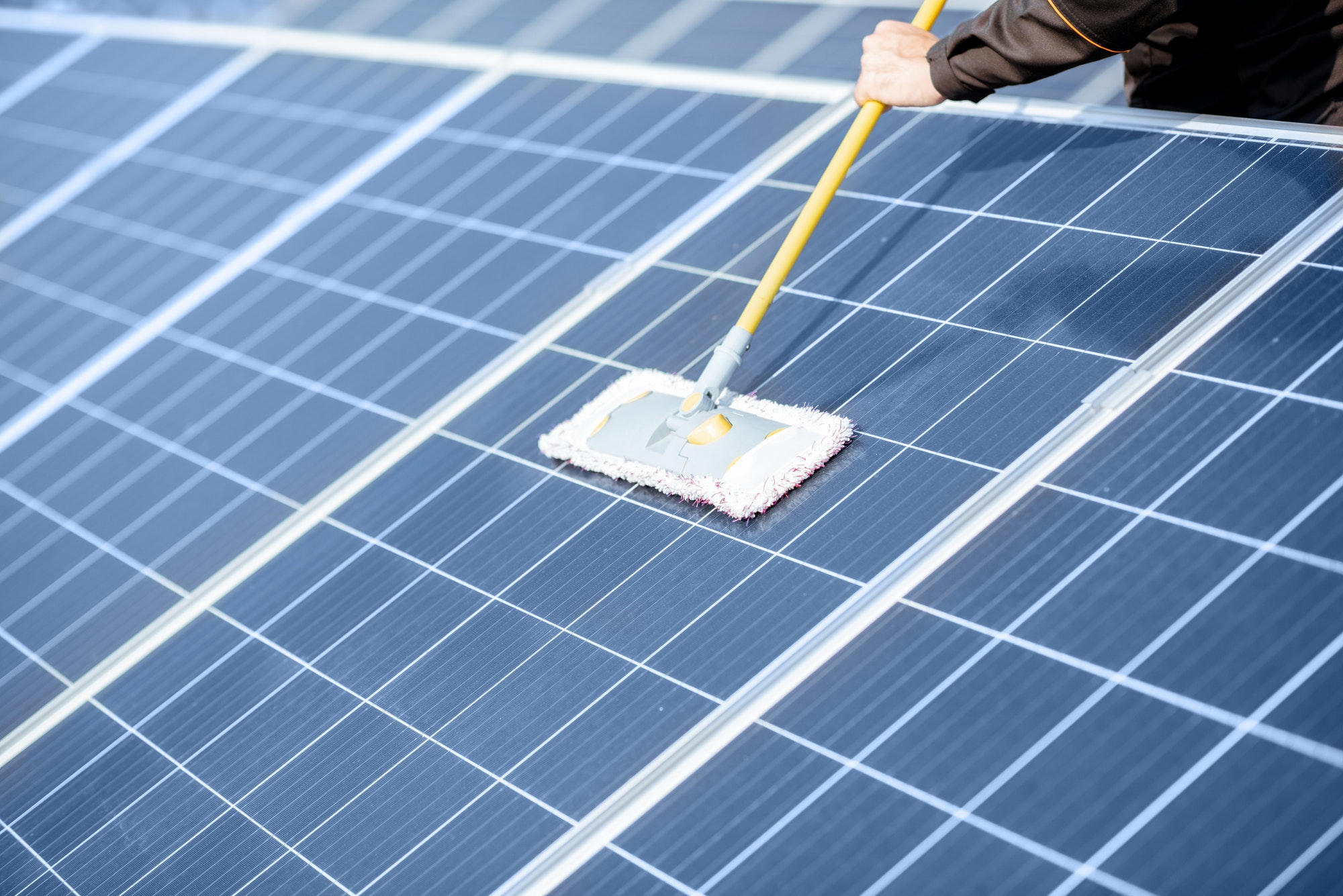 Workman cleaning solar panels
